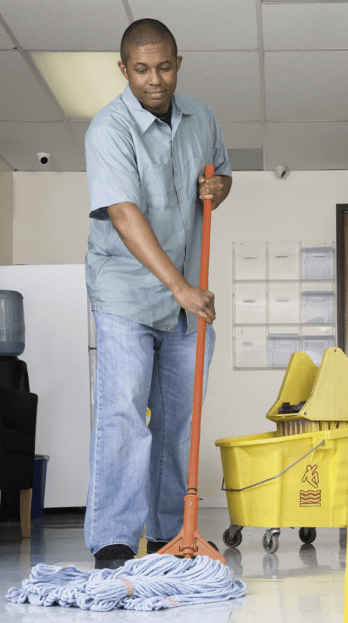 A janitor using a mop and bucket to wash the hallway floor of an office corridor in a Manhattan building.