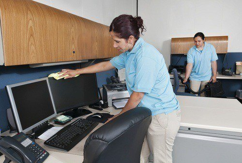 Two maids cleaning a cubicle, one is vacuuming and the other is cleaning a computer monitor